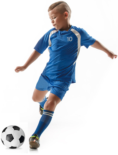 Boy soccer player in blue shirt kicking ball