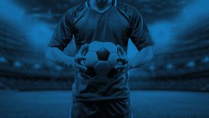 blue background of player holding soccer ball in stadium