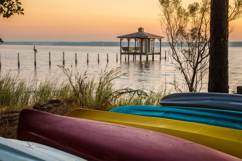 A group of canoes on shore overlooking Mobile Bay