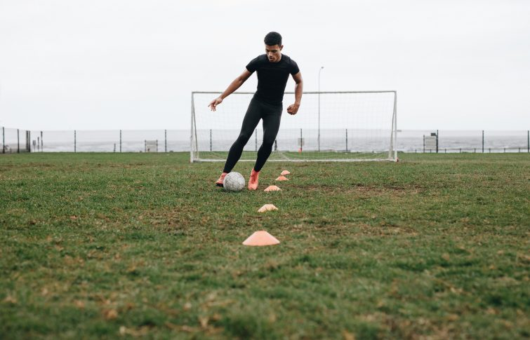 soccer player dribbling cones