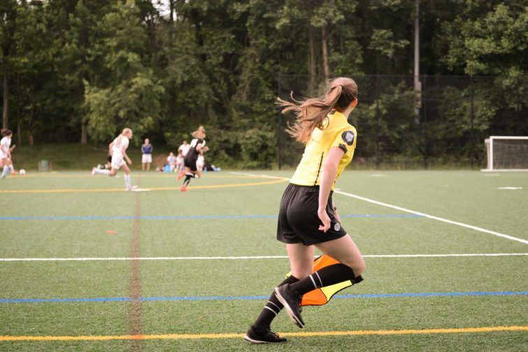 Assistant referee girls running on sideline for offisides