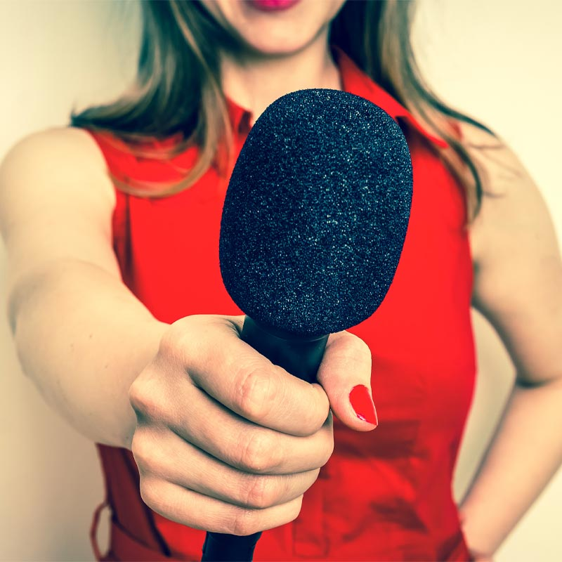woman reporter holding microphone