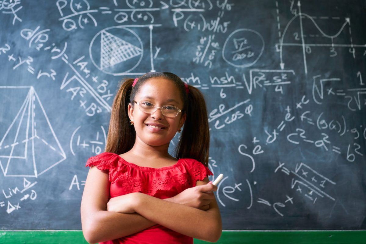 young girl standing in front of math chalkboard