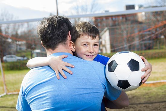 coach dad hug player holding soccer ball